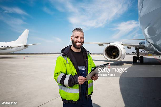Aircraft worker in front of airplane with checklist