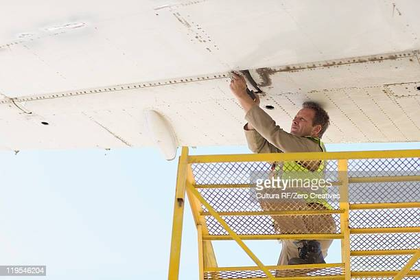Aircraft worker repairing airplane