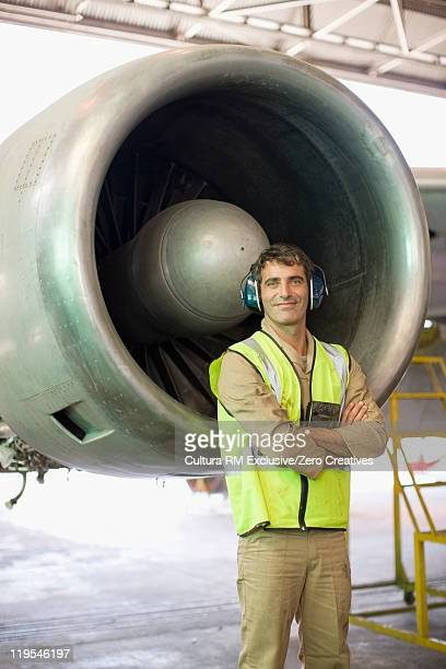 Aircraft worker standing by airplane