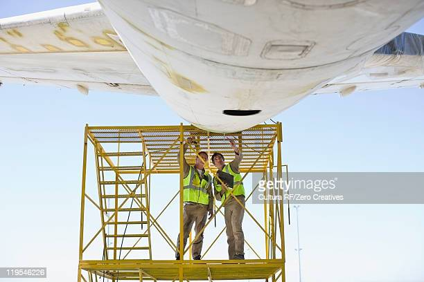 Aircraft workers repairing airplane