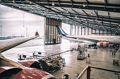 Two wide body aircrafts are parked and servicing in hangar.