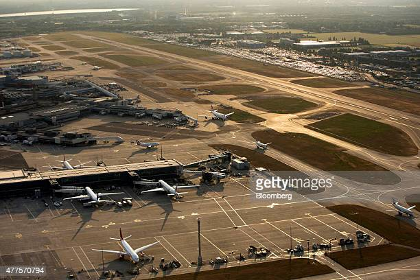 Aircrafts taxi along the perimeter of the north runway center and past passenger terminal buildings at London Heathrow Airport in this aerial...