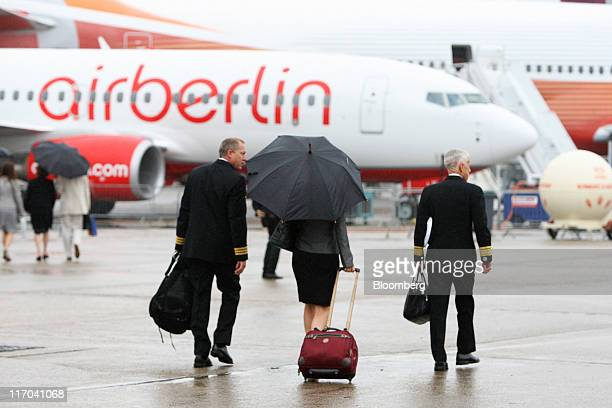 Aircrew walk in the rain towards an Air Berlin aircraft displayed at the Paris Air Show in Paris France on Monday June 20 2011 The 49th International...