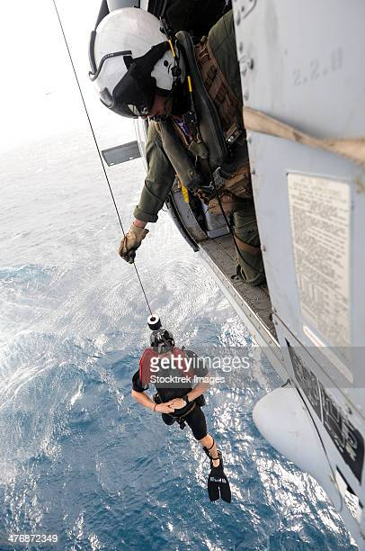 Aircrewman assists in hoisting a member into an MH-60S Sea Hawk.