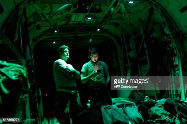 US Airforce crew members stand on September 15 2017 on the back of a C130 cargo plane while taxiing at the Princess Juliana Airport after delivering...