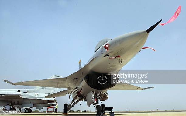 US Airforce officers stands next to the F16 fighter aircraft at the Yelahanka Air Force Station in Bangalore February 8 ahead of the Aero India 2009...