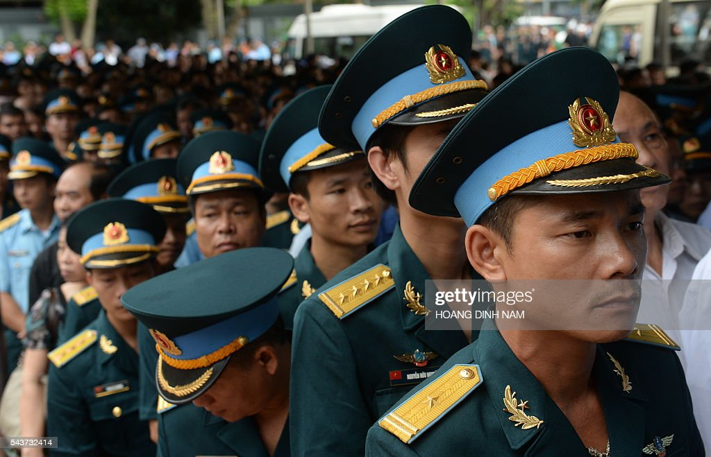 Airforce soldiers line up to pay tribute to victims of a rescue aircraft that crashed on June 16, 2016 over the South China Sea during a search mission for a Vietnamese Airforce Sukhoi SU-30MK2 that went missing two days earlier, during an official funeral ceremony in Hanoi on June 30, 2016. / AFP / HOANG