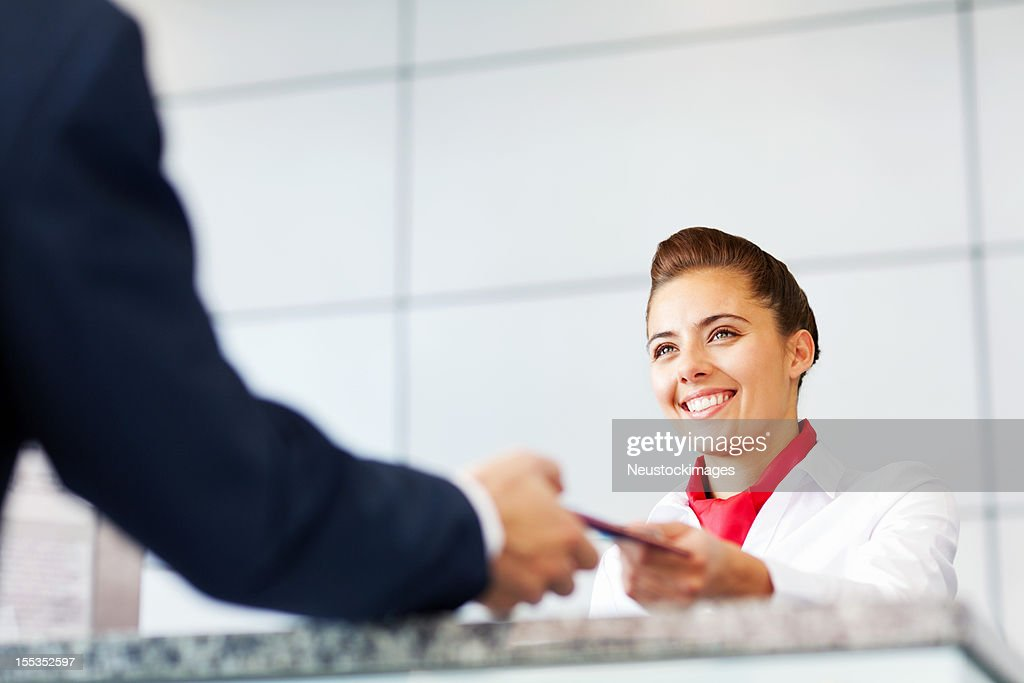 Airline Check In Attendant Handing Tickets To Passenger