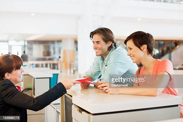 Airline check-in attendant assisting couple at counter in airport