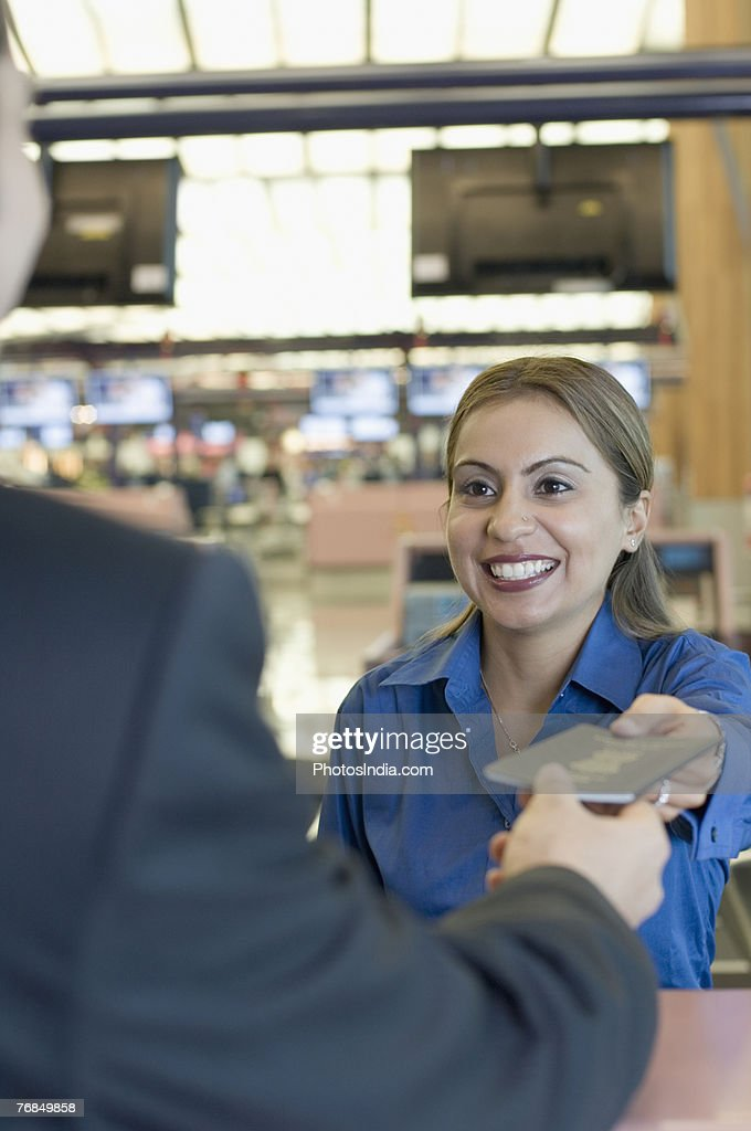 Airline check-in attendant giving a passport to a man at a counter