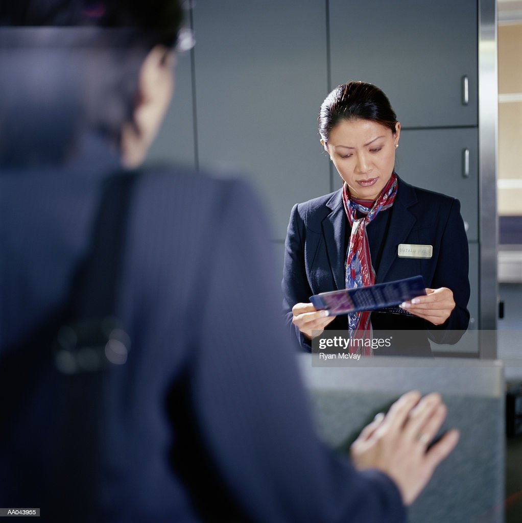 Airline check-in attendant looking at woman's plane ticket