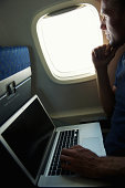 Airline Passenger Sits with Laptop in Window Seat