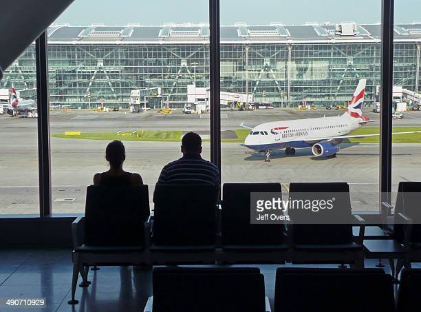 Airline passengers at Heathrow Airport terminal Five terminal 5 B gates looking towards the main terminal building Interiors Silhouette Planes BA...