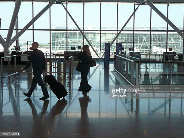 Airline passengers at Heathrow Airport terminal Five terminal 5 B gates looking towards the main terminal building Interiors Silhouette