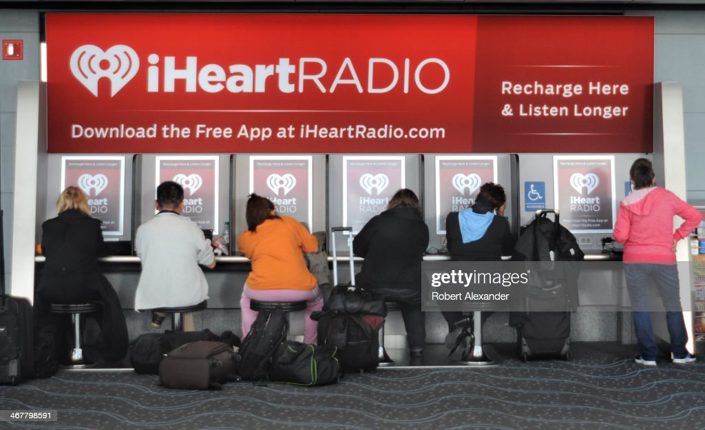 Airline passengers between flights patronize the iHeartRadio facility at Denver International Airport in Denver, Colorado. iHeartRadio is an internet radio platform owned by Clear Channel Broadcasting Inc.