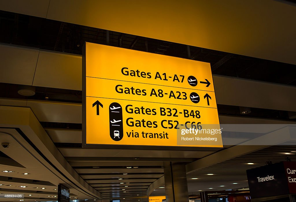 Airline passengers follow signs for their flight departures March 13, 2014 at London, England's Heathrow Airport.