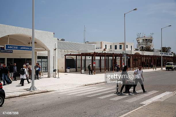 Airline passengers pull their luggage across a pedestrian crossing outside Santorini airport on the island of Santorini Greece on Thursday May 21...