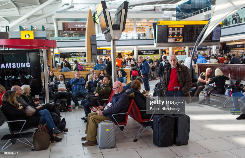 Airline passengers wait for their flight departures March 13, 2014 at London, England's Heathrow Airport in Terminal 5.