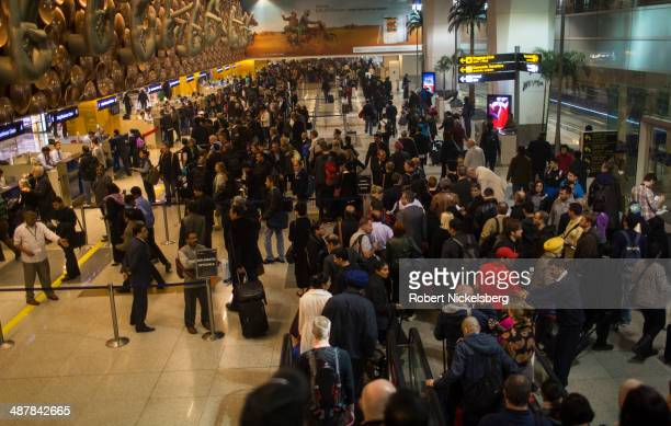 Airline passengers wait in line at immigration and passport control February 19 2014 at Indira Gandhi International Airport in New Delhi India