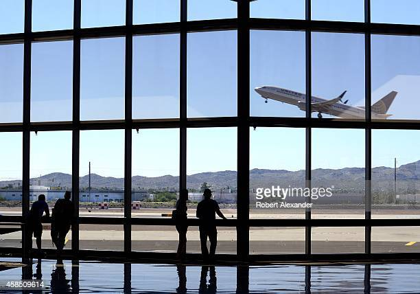 Airline passengers waiting for their flights watch from the terminal as a United Airlines airplane takes off at Phoenix Sky Harbor International...