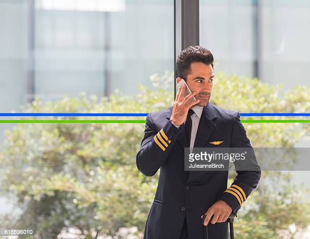 Airline pilot taking a call before travel