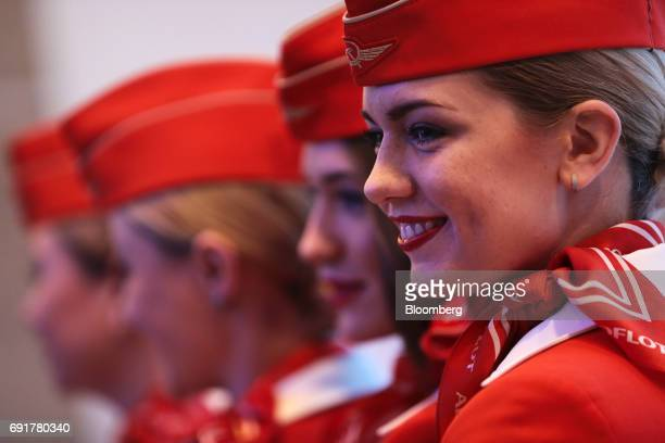 Airline staff from AeroflotRussian Airlines PJSC pose for photographs during the St Petersburg International Economic Forum at the Expoforum in Saint...