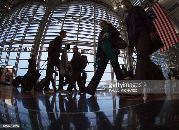 Airline travelers at Ronald Reagan National Airport in Arlington Virginia walk to a Transportation Security Administration security checkpoint prior...