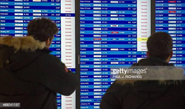 Airline travelers check the status of flights that are mostly cancelled at Dulles International Airport February 13 near Washington DC in Sterling...