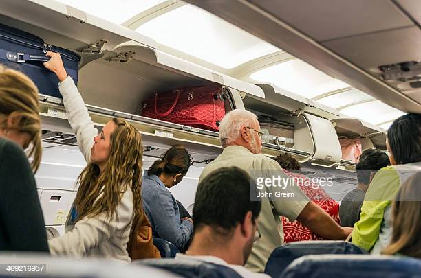 Airline travelers retrieve their carryon luggage from overhead compartments