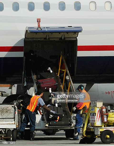 Airline workers load luggage and cargo into a US Airways passenger plane at Los Angeles International Airport on October 30 2010 in Los Angeles...
