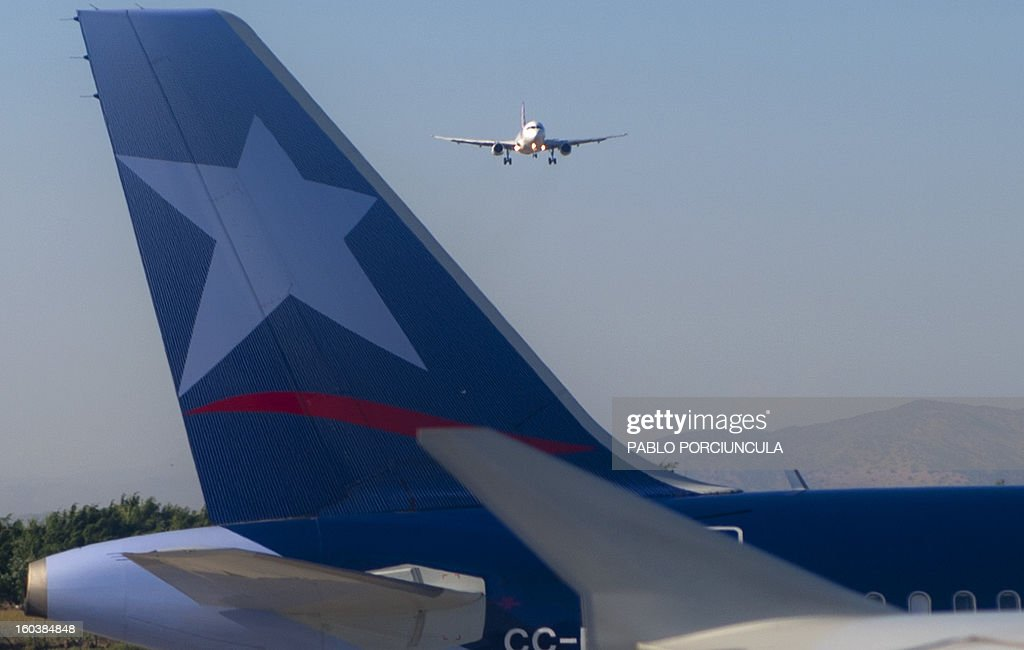 A TAM airliner lands at Santiago's airport while another from LAN sits on the tarmac on January 29, 2013. AFP PHOTO/Pablo PORCIUNCULA