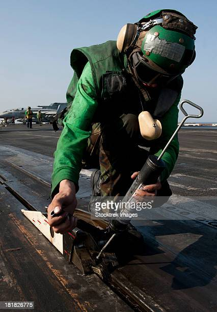 Airman greases the catapult shuttle on USS John C. Stennis.