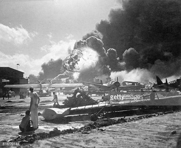 Airmen at the Ford Island Naval Air Station watch smoke and flames billow from the USS Shaw which had just been blown up by Japanese bombers during...