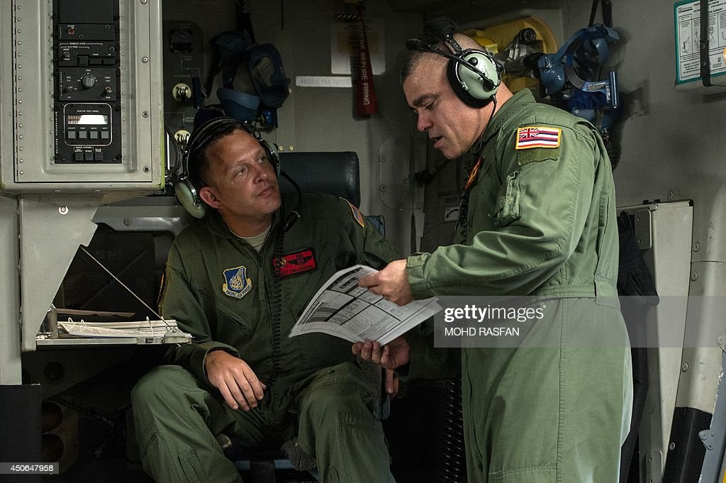 US airmen discuss plans as they take part in the combat search and rescue exercise 'Cope Taufan' onboard a C-17 aircraft over Malaysia on June 15, 2014. The US Air Force and the Royal Malaysian Air Force participated in exercise Cope Taufan 14 to improve combined readiness and cooperation between the two countries.