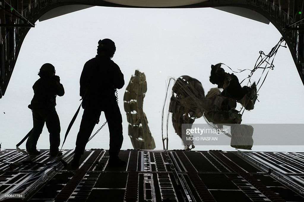 US airmen drop supplies as part of the combat search and rescue exercise 'Cope Taufan' onboard a C-17 aircraft over Malaysia on June 15, 2014. The US Air Force and the Royal Malaysian Air Force participated in exercise Cope Taufan 14 to improve combined readiness and cooperation between the two countries.