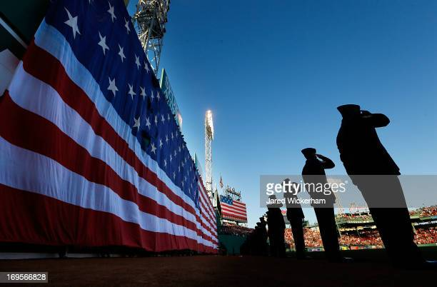 Airmen from the Hanscom Air Force Base stand and salute in front of the large American flag unfurled over the Green Monster during the singing of the...