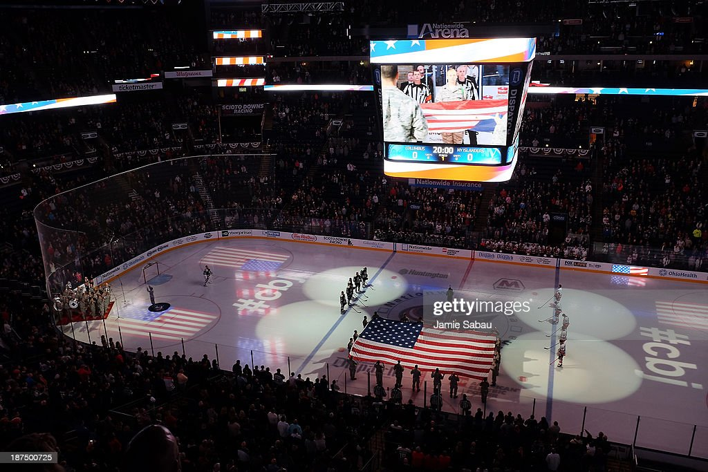 Airmen from Wright-Patterson Air Force Base present the American flag while the 338th U.S. Army Band performs the National Anthem on Military Appreciation Night prior to the game against the Columbus Blue Jackets and New York Islanders on November 9, 2013 at Nationwide Arena in Columbus, Ohio.