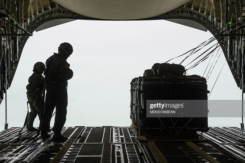 US airmen prepare to drop supplies as part of the combat search and rescue exercise 'Cope Taufan' onboard a C-17 aircraft over Malaysia on June 15, 2014. The US Air Force and the Royal Malaysian Air Force participated in exercise Cope Taufan 14 to improve combined readiness and cooperation between the two countries.