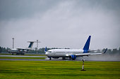 Passenger airplane arrives at the airport in rain