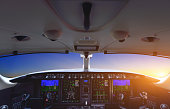 Airplane cockpit in sunset sky.