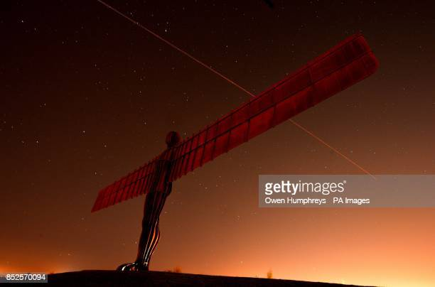 A airplane flies over the Angel of the North in Gateshead Tyne and Wear as temperatures dropped to near freezing overnight