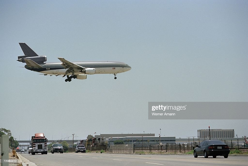 Airplane flying above multiple lane highway