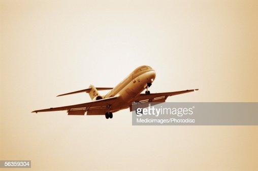 Airplane flying in hazy sky