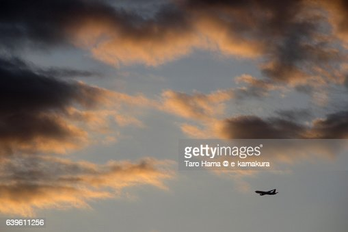 Airplane flying in the sunset cloud