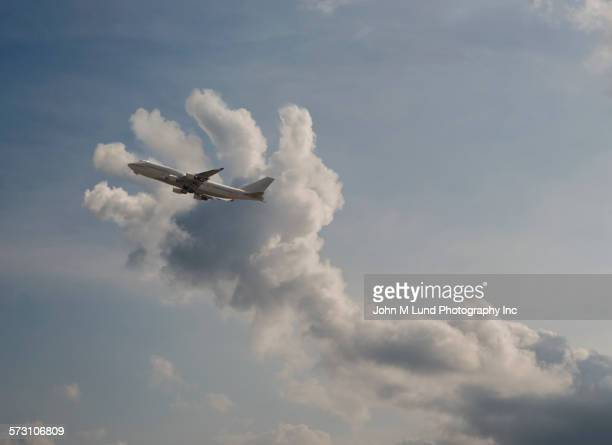 Airplane flying into clouds in shape of hand