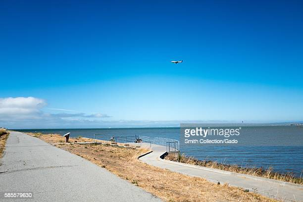 Airplane flying low on approach to San Francisco International Airport with San Francisco Bay visible in Seal Point Park San Mateo California July...