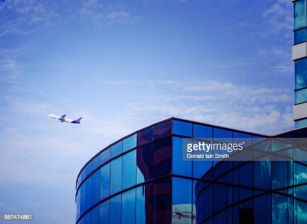 Airplane flying over airport tower