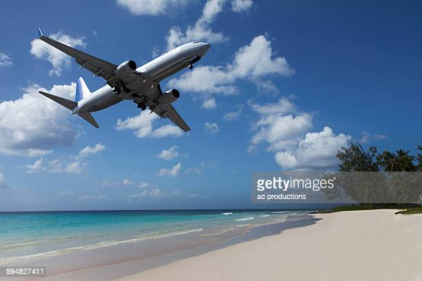 Airplane flying over tropical beach