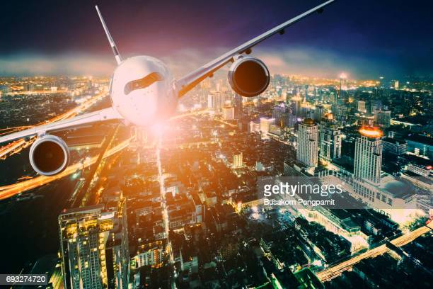 Airplane for transportation flying over the city at night scene, city on beautiful sunset background