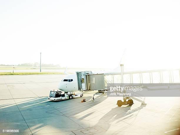 Airplane in airport runway against clear sky